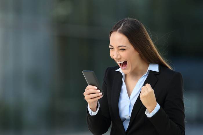 Well-dressed businesswoman fist-pumps in excitement over news she is reading on her smartphone.