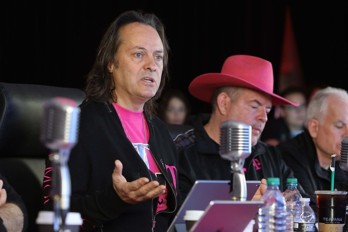T-Mobile CEO John Legere and CFO Braxton Carter sitting behind a desk covered in microphones, water bottles, and laptops.