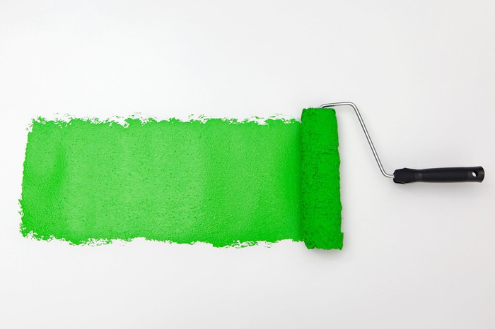 A paint roller adding lime green paint to a white wall