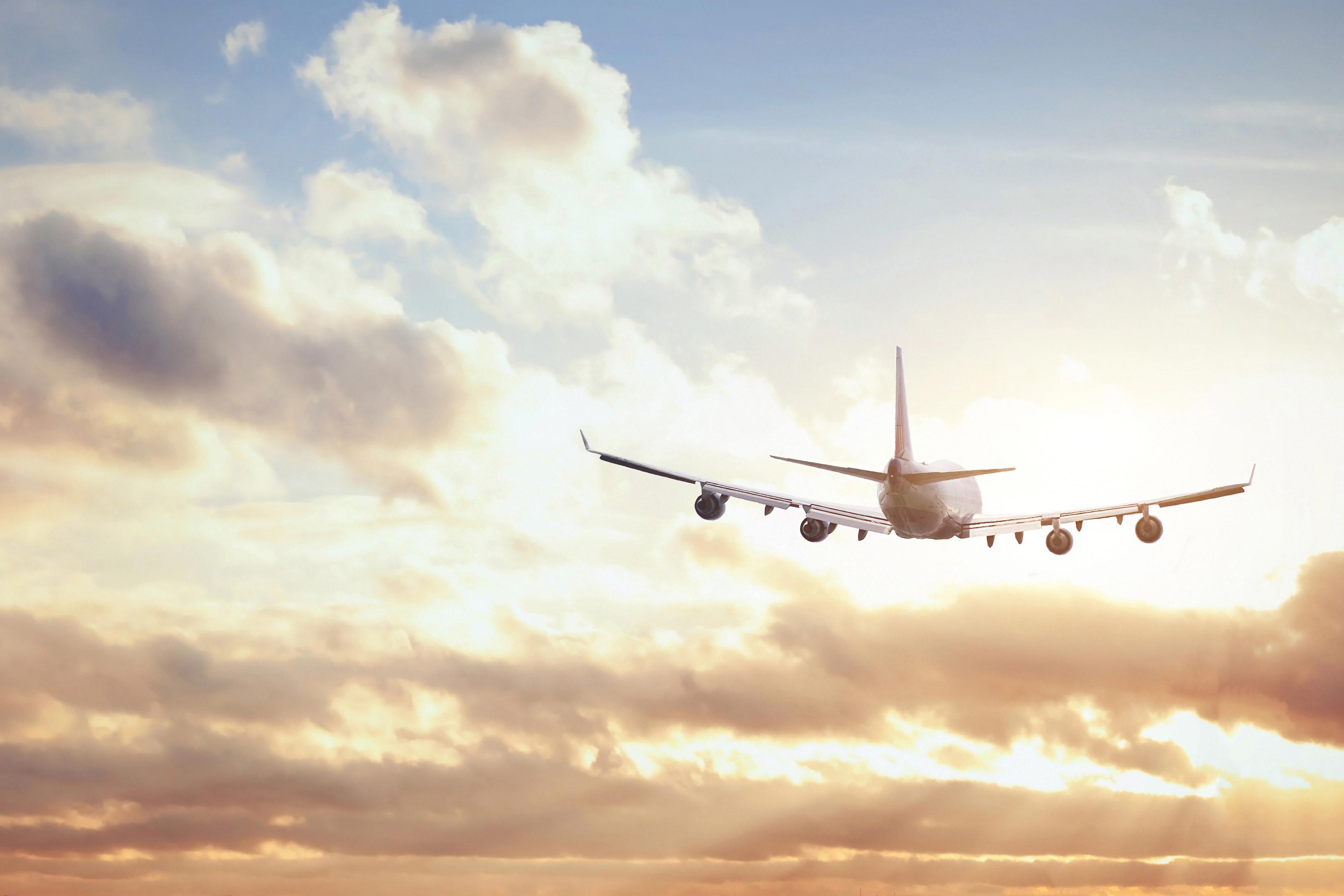 Plane flying below clouds.