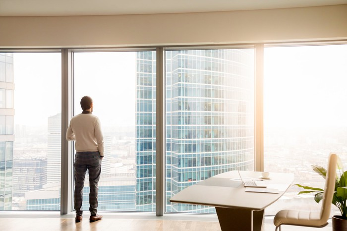 A man looking out of a skyscraper office window.