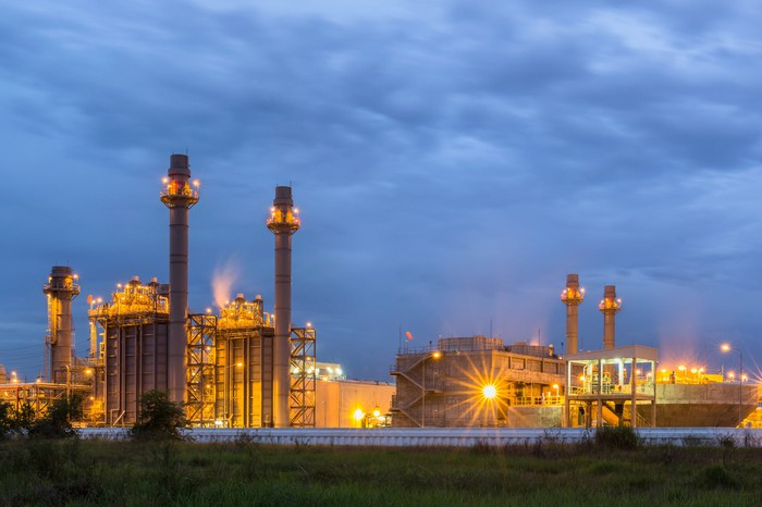 Power plant with lights on at dusk