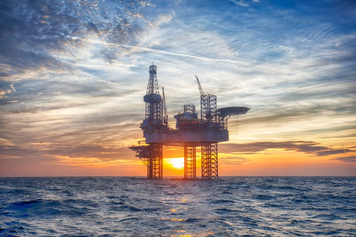 An offshore drilling rig at sunset.