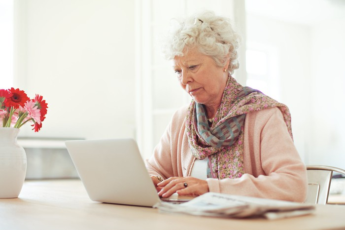 Older woman sitting at a table while typing on a laptop