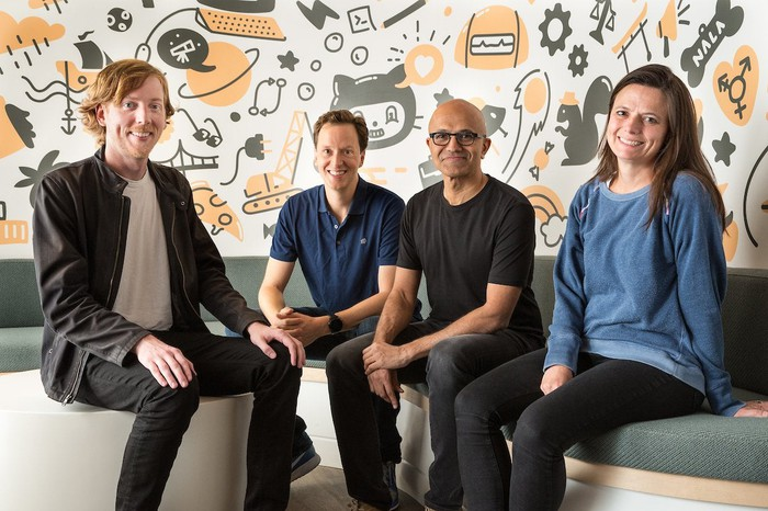 The co-founder of GitHub, sitting with three executives from Microsoft at GitHub headquarters