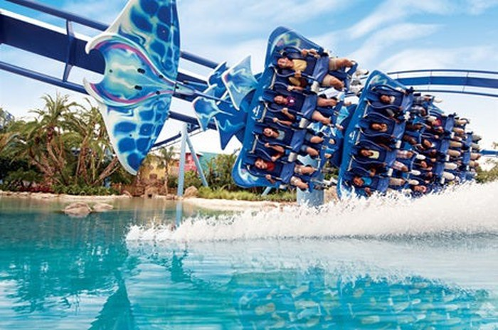 A roller coster is shown going over water.