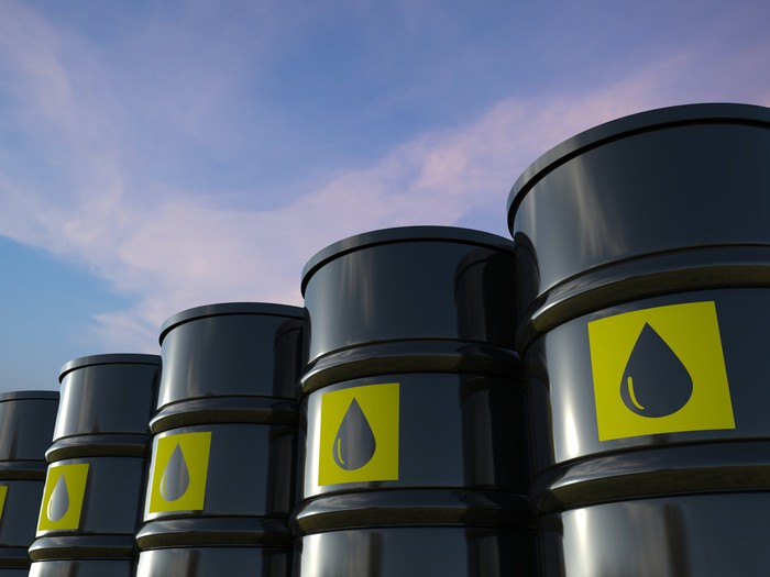 Barrels of crude oil lined up in a row.