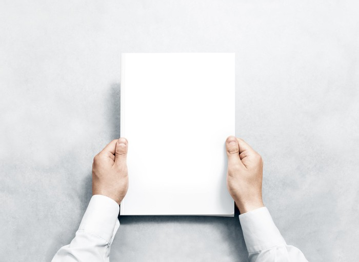 A man holds a blank piece of paper.