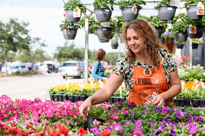 A Home Depot garden department employee works with plants