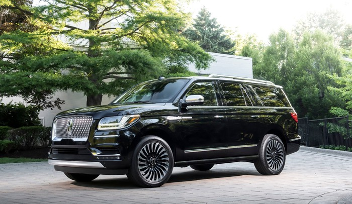 A black 2018 Lincoln Navigator, a large, truck-based luxury SUV with dramatic nautical-inspired styling, is shown on a country road.
