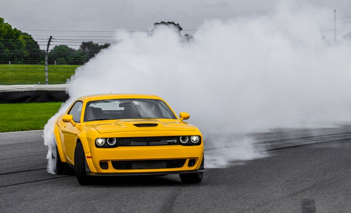 A bright yellow 2018 Dodge Challenger SRT Hellcat Widebody is shown powering through a cloud of tire smoke on a race track.