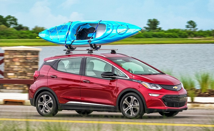 A red Chevrolet Bolt EV, an upright small hatchback, with a kayak on its roof, driving near a lake.