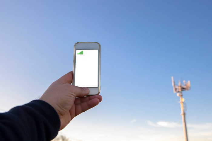 A man points a smartphone towards a cell tower.