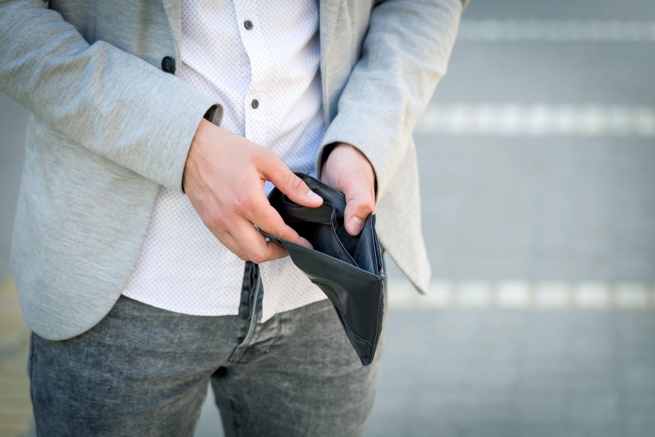 Man holding open a wallet to reveal that it's empty