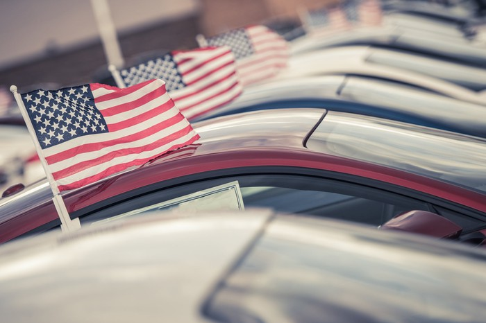 Row of cars at a dealership with American flags on the windows.