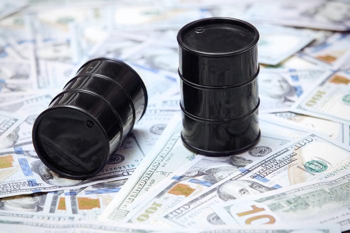 Two miniature oil barrels on top of $100 bills.