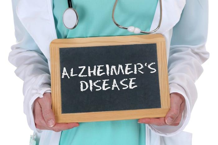 "Physician holding chalkboard with ""Alzheimer's disease"" written on it"