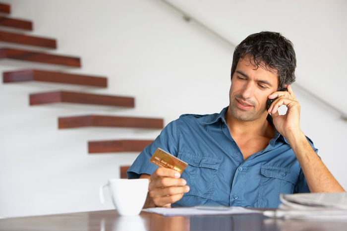 Man holding credit card talking on the phone