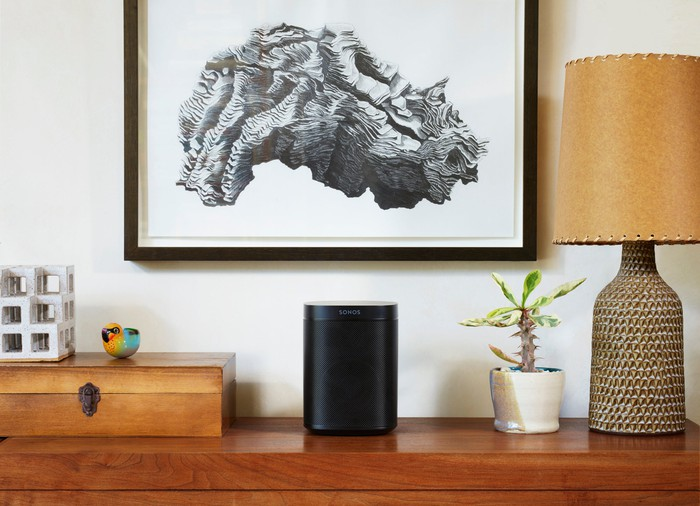 Sonos One sitting on a shelf beneath a painting