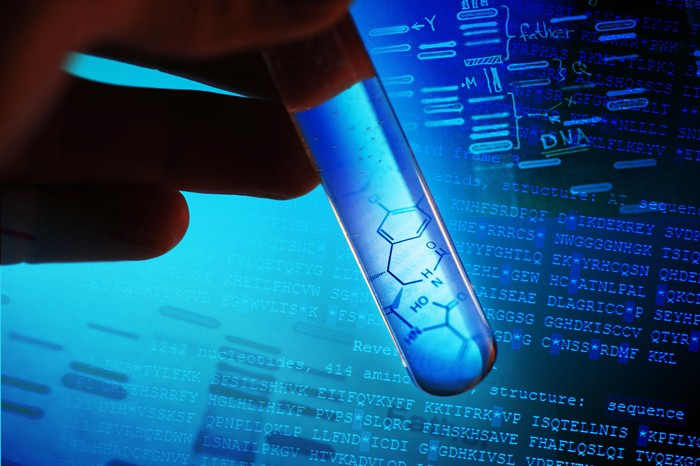 Hand holding test tube with DNA sequences and chemical structures in background