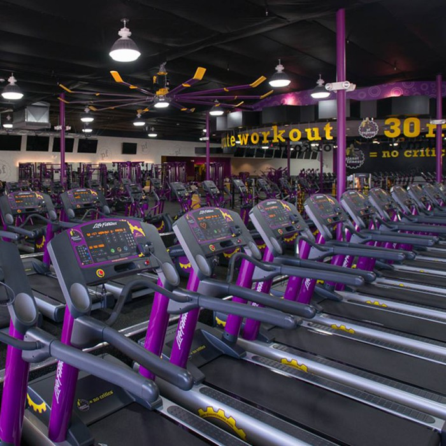Row of treadmills inside a Planet Fitness location