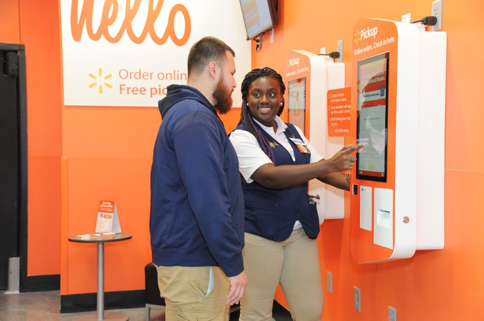 A Walmart associate helping a customer with an in-store pickup.
