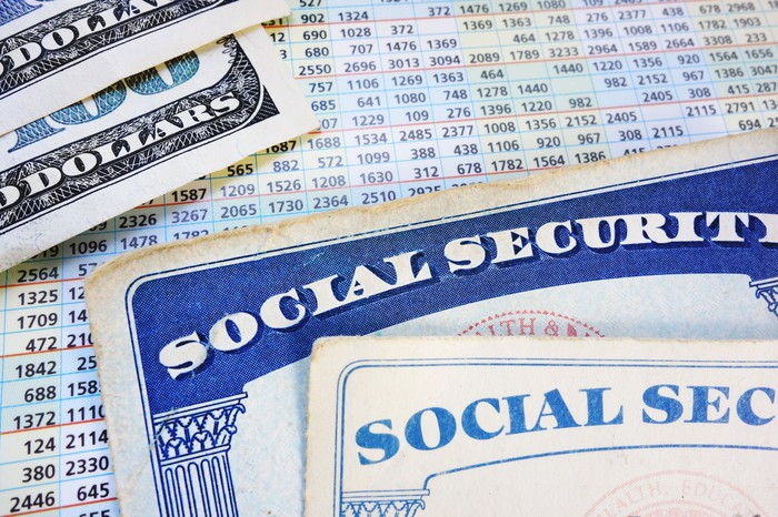 Two Social Security cards lying next to hundred dollar cash bills, and on top of a Social Security payout card.
