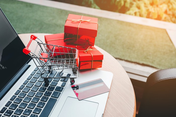 A miniature shopping cart, three small present boxes, and a credit card sitting on top of a laptop.