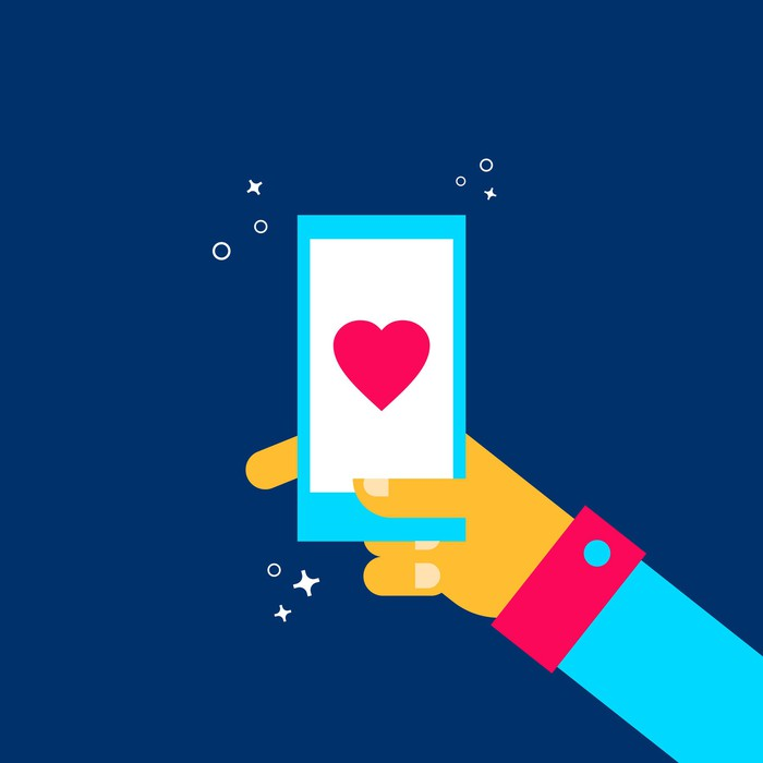 An illustration of a hand holding a mobile phone displaying a heart.