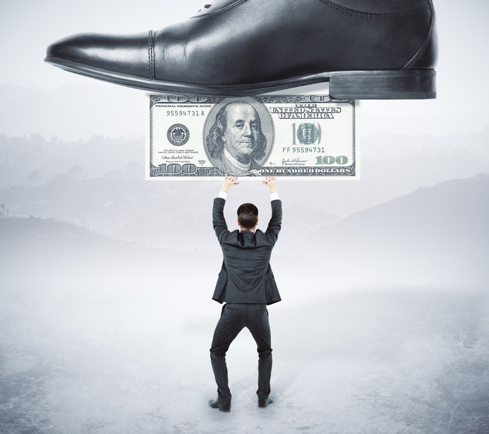 A miniature businessman attempting to hold up a hundred dollar bill which is being stepped on by a much larger shoe, representing big business.