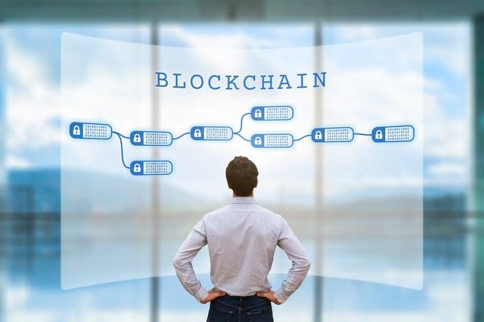 A businessman looking at an encrypted blockchain on a digital board.