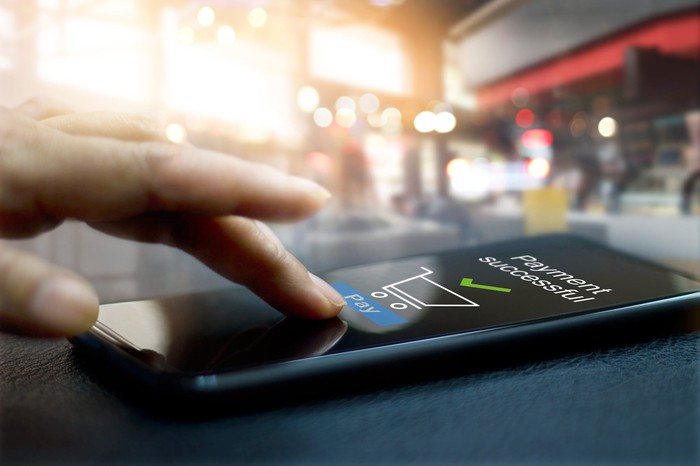 Fingers making a digital payment on a mobile phone