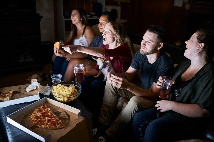 Friends watching TV and eating pizza together.