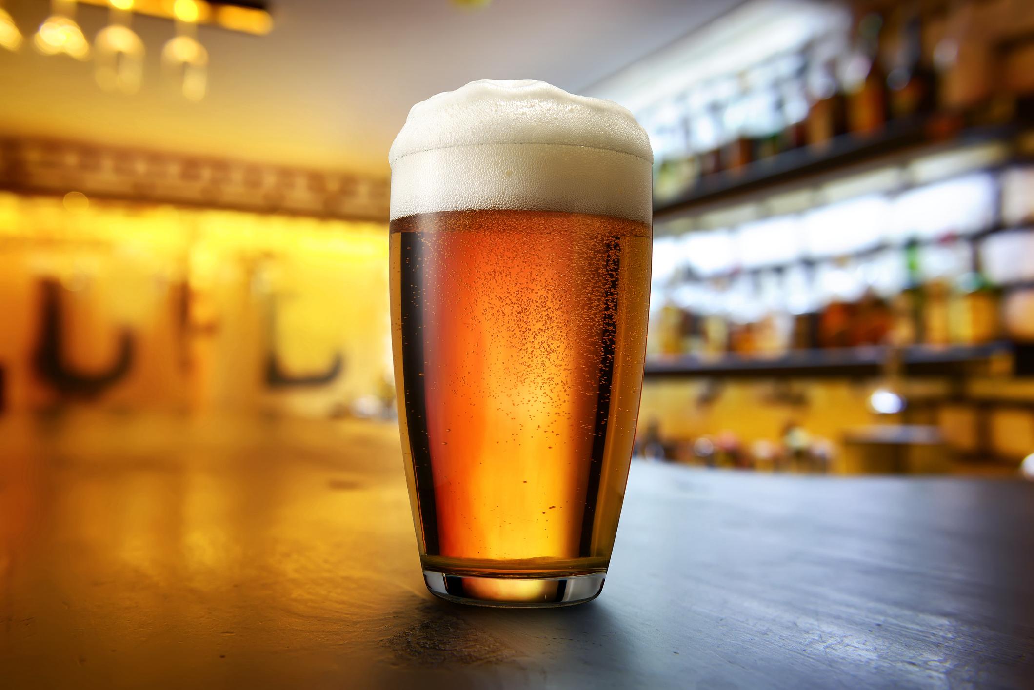 Single beer glass on a bar.