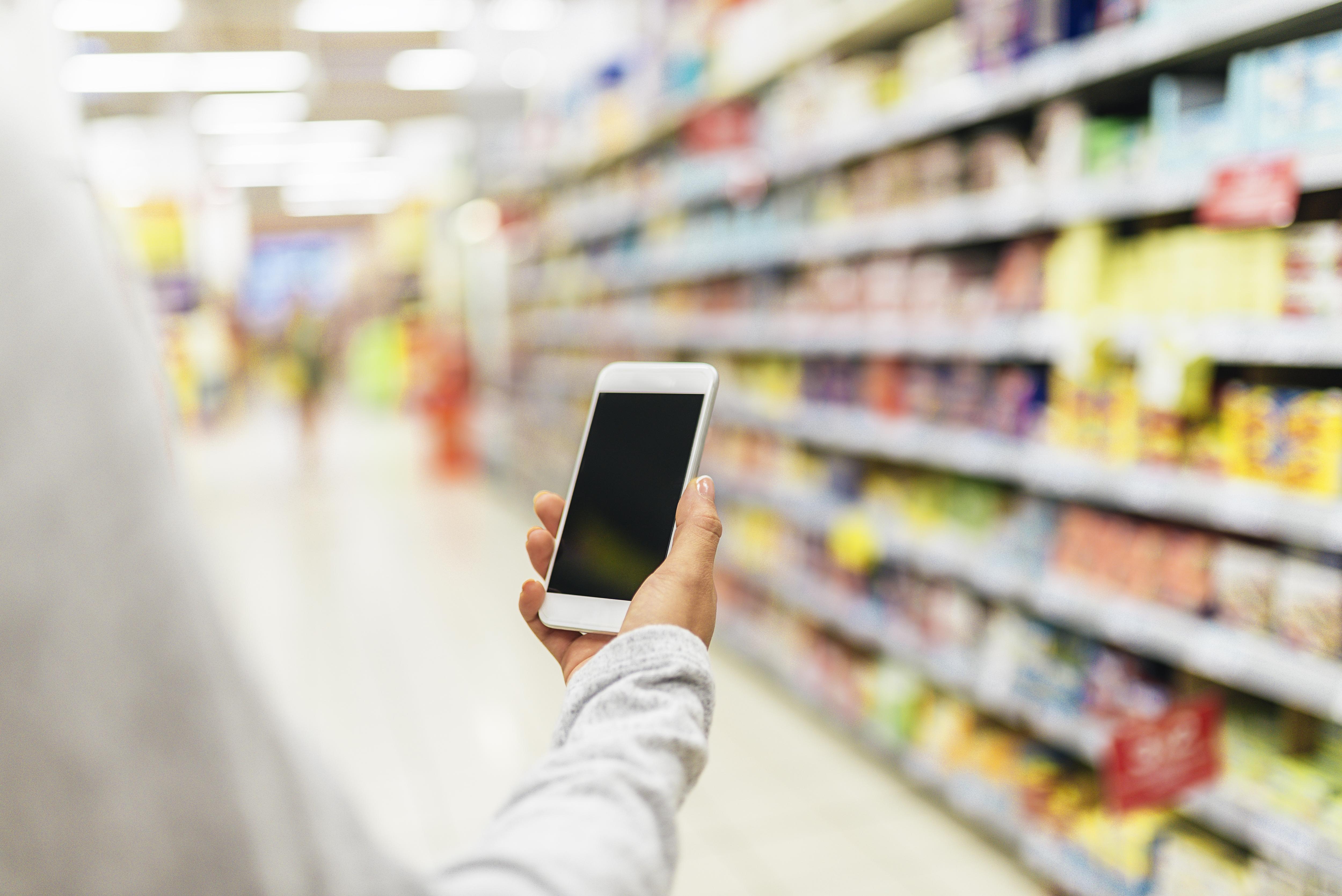 A man checks his smartphone while shopping.