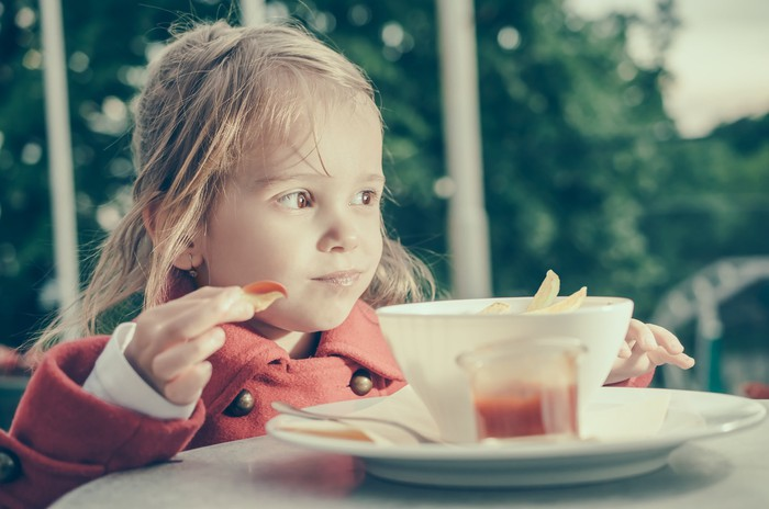 A girl eating French fries she just dipped in ketchup.