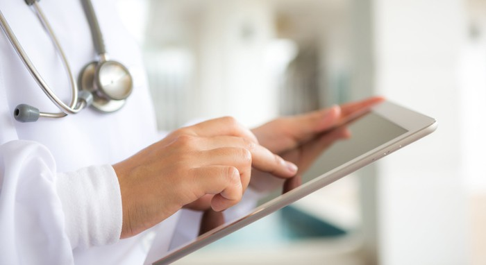 A doctor touches the screen of an iPad.