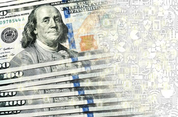 A fanned stack of hundred dollar bills transforming into digital money.