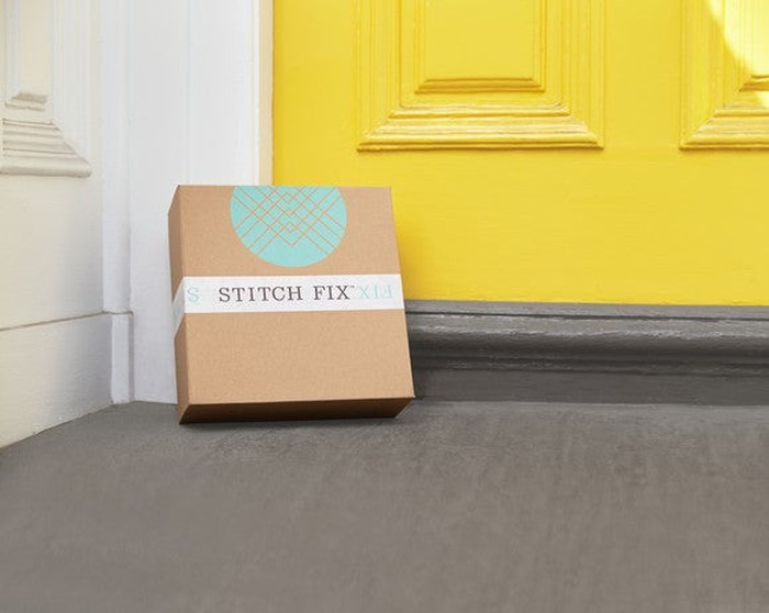 Stitch Fix box leaning on a yellow door