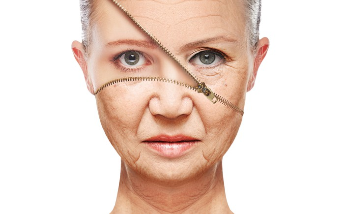 Older woman with zipper on face partially unzipped revealing younger woman