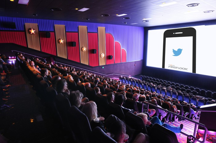 A movie theater filled to capacity, showing the logo of National CineMedia's FirstLook service on the screen.