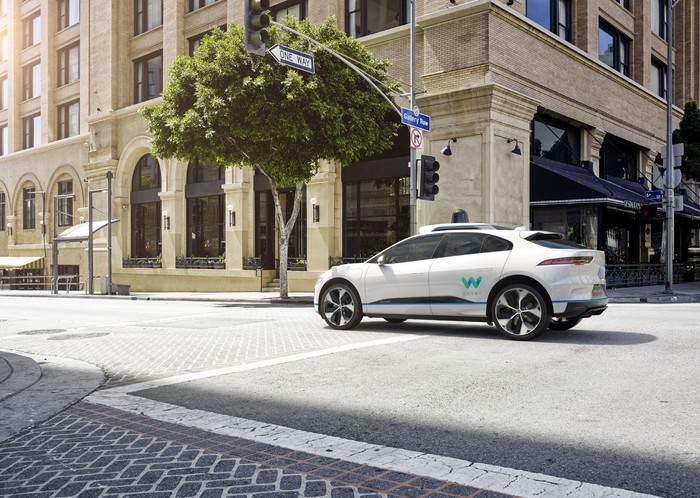 A white Waymo Jaguar iPace crossing an intersection.
