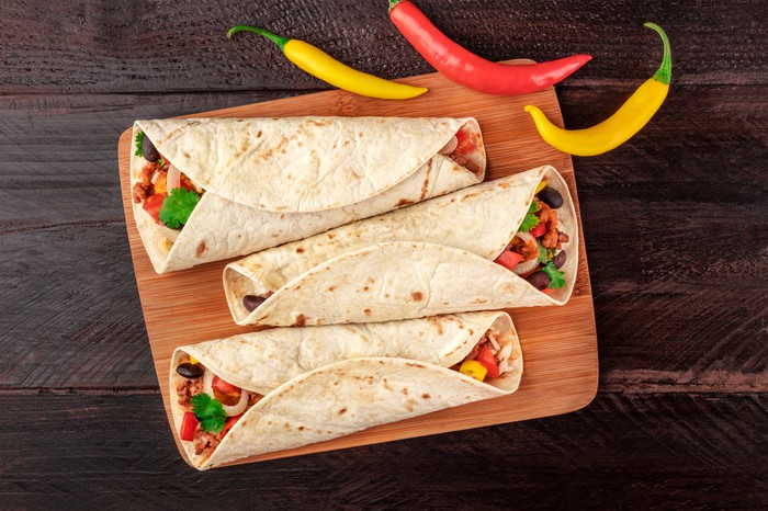 3 burritos on a plate with peppers on the side