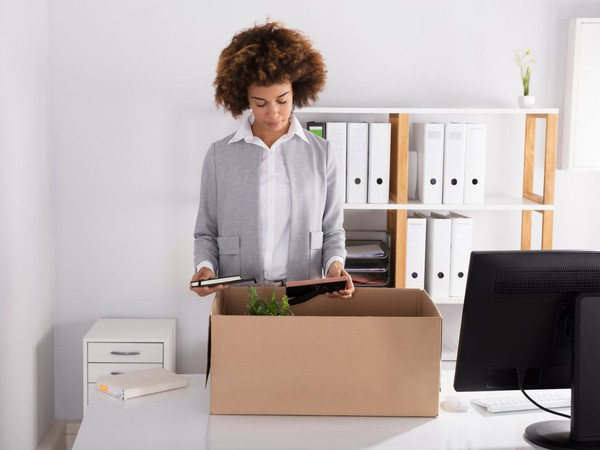 professional female packing up a desk_GettyImages-905726828