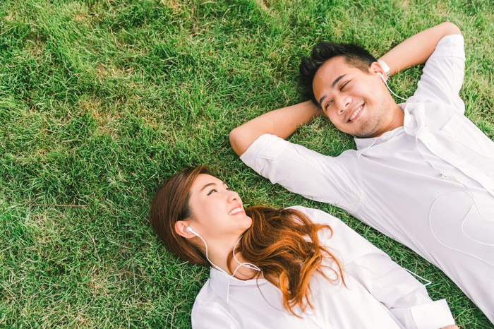 A Chinese couple laying on grass listening to music