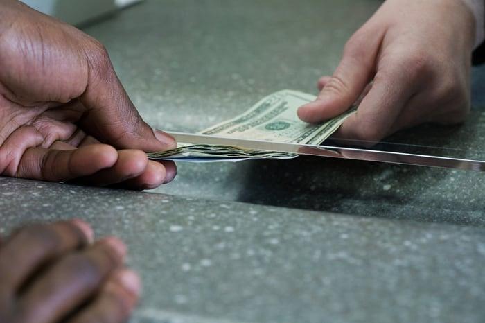 Money being passed under a glass window.