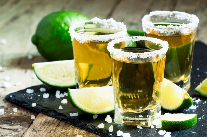 Three shot glasses of tequila with salt and lime