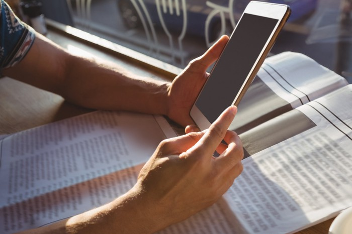 A person holds a tablet over a newspaper.
