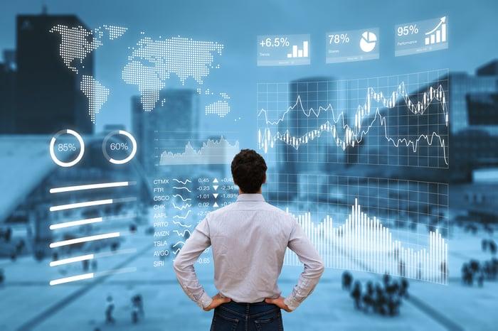 Man looking at stock charts on a big screen