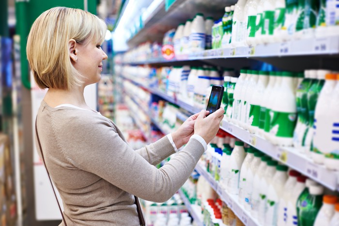 Woman taking a picture of grocery products at a supermarket.